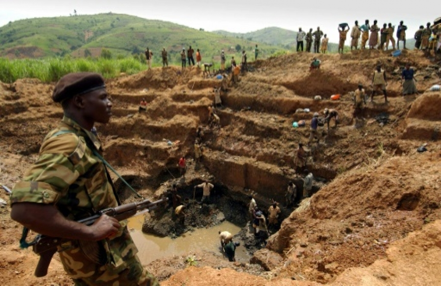 Un milicien surveille les ouvriers d'une mine d'or u00e0 ciel ouvert en Ituri, dans le nord-est de la RD Congo, le 18 juin 2003   AFP/Archives   ERIC FEFERBERG