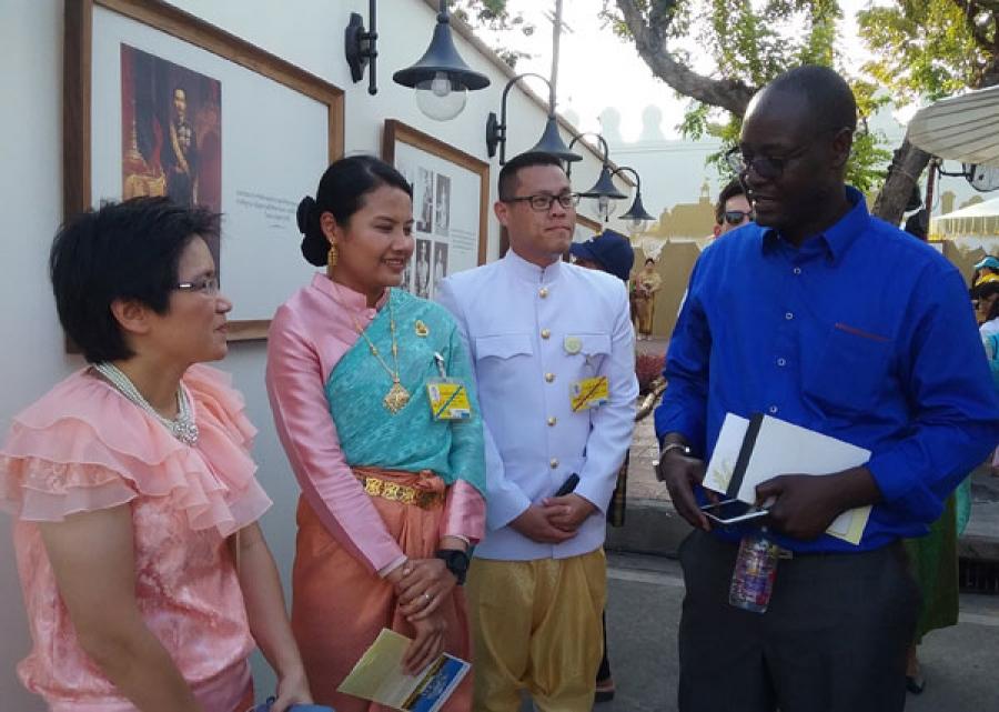 Des festivaliers, du00e9guisu00e9s en tenue traditionnelle Thau00ef u00e9changent avec le confru00e8re du Su00e9nu00e9gal.