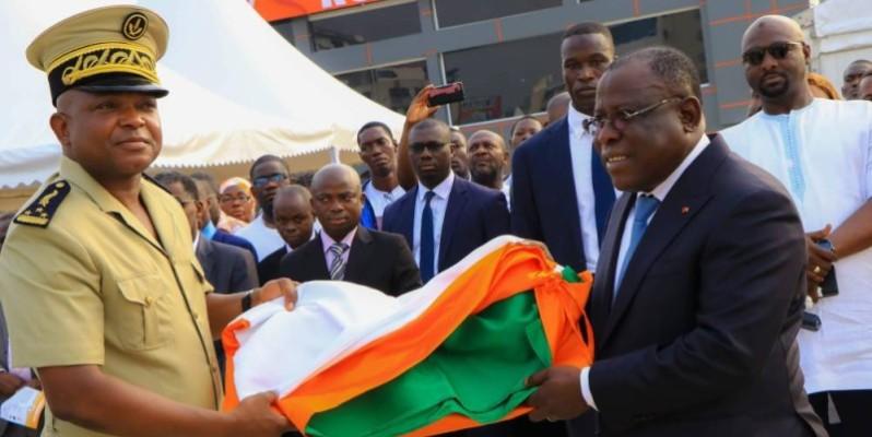 Le préfet d'Abidjan et le maire de Koumassi tenant le drapeau. (DR)