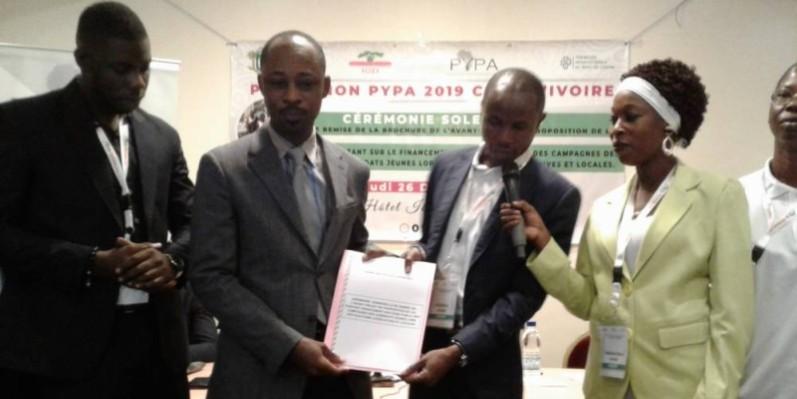 Légende : Kouamé Fils David recevant la brochure d'avant-projet de loi des mains de Fidel Kassi, coordonnateur du '' Program Pypa 2019''.(DR)