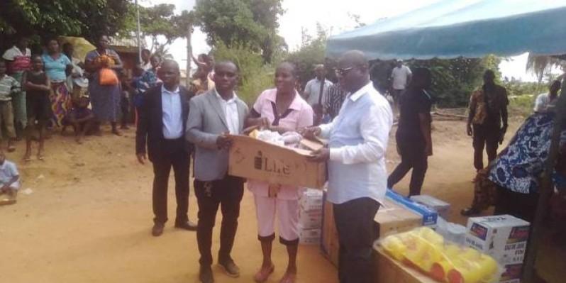 Le ministre Emmanuel Essis (en blanc) remettant un carton de sucre au Dr Konin Amoa Thomas, médecin-chef du centre de santé de Toupah. (DR)