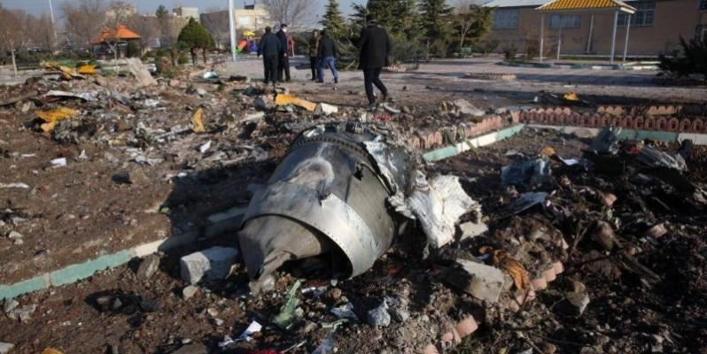 Des secouristes marchent au milieu des débris du vol PS752 de l'Ukrainian International Airlines le 8 janvier 2020. (AFP)