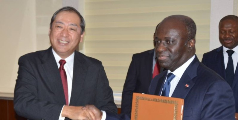 Échange de parapheurs entre Marcel Amon-Tanoh (à droite) et l'ambassadeur du Japon. (Julien Monsan)