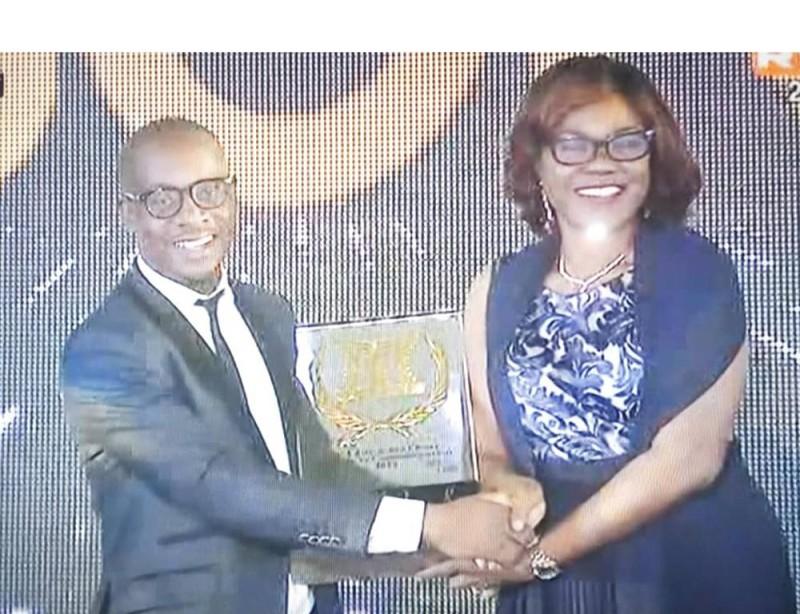 Serge Koléa recevant son trophée des mains de la ministre Kaba Nialé qui a représenté le Premier ministre, parrain de la cérémonie