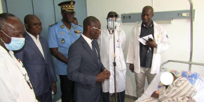 Le ministre Diomandé Vagondo et le directeur général de la police nationale, au chevet de l'agent blessé. (Dgpn)