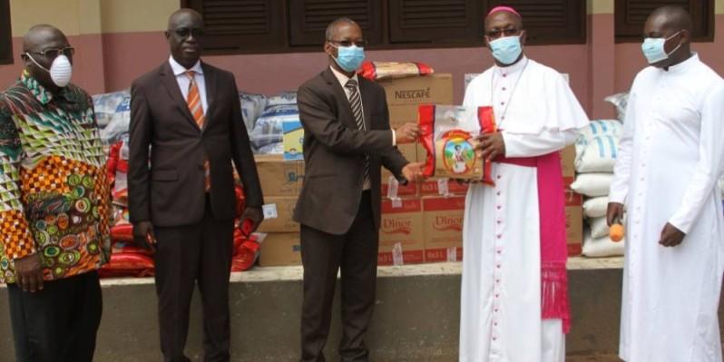 Mgr Jean Salomon Lézoutié (à droite) recevant symboliquement le don des mains de Coulibaly Issifou. (DR)