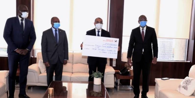 Adama Coulibaly, ministre de l'Economie et des Finances, recevant le chèque de 200 millions de Fcfa de l'Atlantic Business International. (DR)