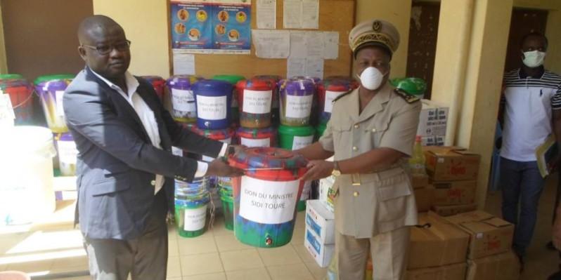 Ali Diabaté (à gauche), représentant le ministre Sidi Touré, remet symboliquement le kit sanitaire à Jules Gouessé, préfet de Béoumi. (CHARLES KAZONI)