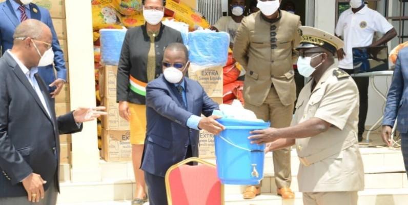 Le préfet de région recevant un échantillon du don des mains du ministre Joseph Séka Séka sous le regard du Président du Conseil régional Patrick Achi. (DR)