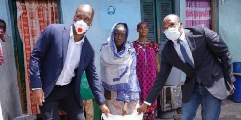 Traoré Salif dit A'Salfo et Didier Drogba remettant symboliquement un sac de riz à une famille. (Dr)