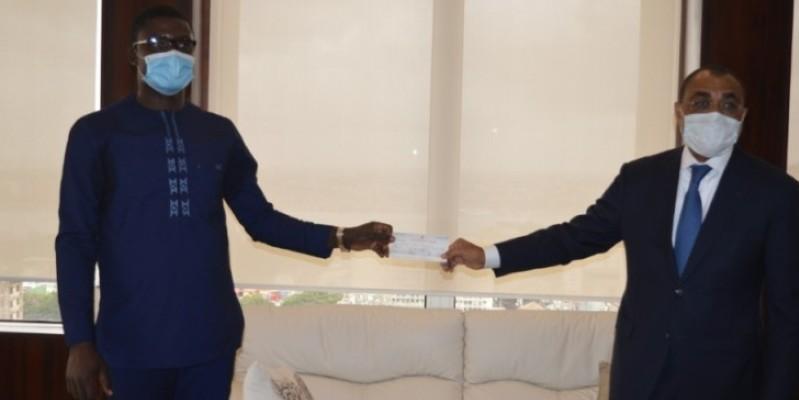Le ministre de l'Économie et des Finances, Adama Coulibaly (à droite), réceptionnant les chèques des entreprises donatrices. (Dr)