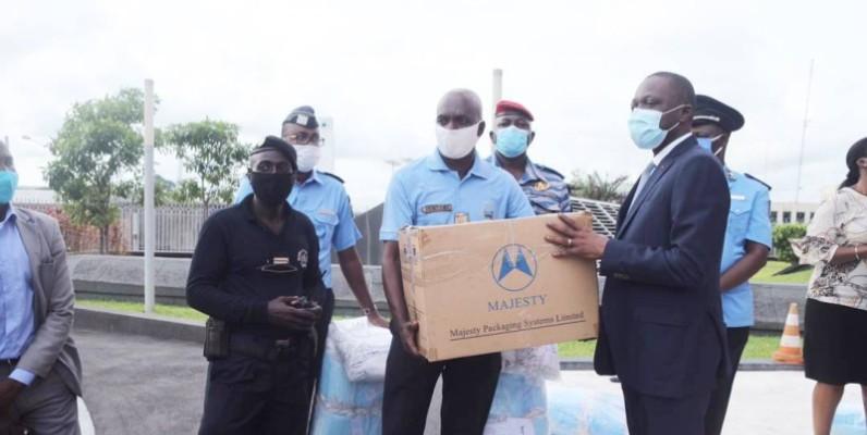 Remise symbolique des cache-nez aux forces de l'ordre par le ministre des Transports, Amadou Koné (à droite). (DR)