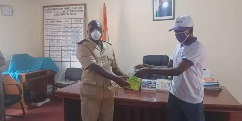 Le vice-président de l'Ong Dokatiéné Silué remettant du gel hydro-alcoolique au préfet du département Sinfra,Yahaya Coulibaly. (DR)