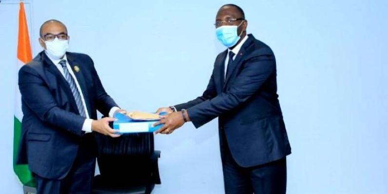Le ministre Soulyemane Diarrassouba remettant le don du Premier ministre au maire de Lakota. (DR)