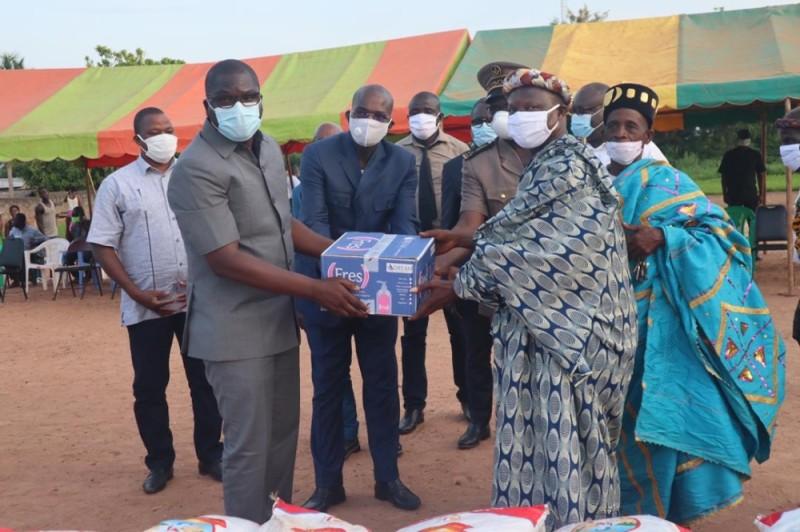Amedé Kouakou remettant des présents aux populations de Bocanda, après la cérémonie d'inauguration du siège du Rhdp de la ville. (photo : DR)