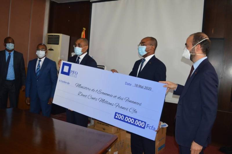 Les ministres Claude Isaac Dé (au centre) et Adama Coulibaly (à gauche) recevant le chèque des mains du directeur général du groupe Pfo, Clyde Fakhoury. (Dr)