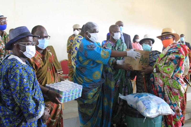 Beugré Mambé remettant un échantillon du don à un chef de village bénéficiaire. (Photo: SEBASTIEN KOUASSI)