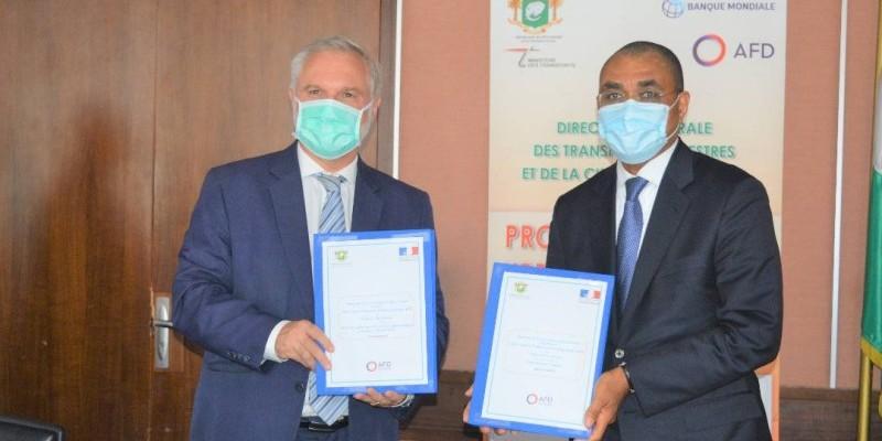 Echange de parapheurs entre le ministre Adama Coulibaly (à droite) et l'Ambassadeur de la France en Côte d'Ivoire, Gilles Huberson. (DR)