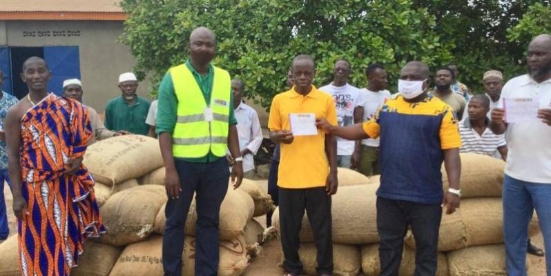 Des producteurs de noix de cajou heureux de brandir leurs reçus après la vente de leurs produits. (DR)
