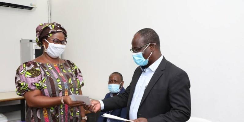 Venance Konan remet un bon d'achat à Aly Kouamé Colette épse Yao, la présidente de l'Association des femmes de Fraternité Matin. (Photo: Bosson Honoré)