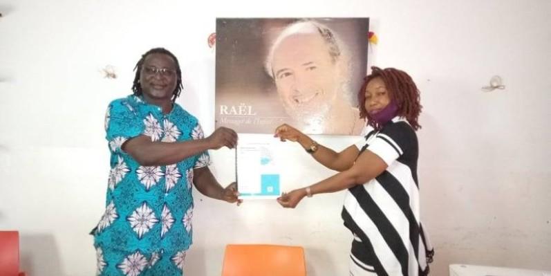 Le guide national Yves Boni recevant le document de synthèse des travaux sur la surpopulation en Côte d'Ivoire des mains de Julie Kuyo, la responsable de la cellule Femme du mouvement Raélien Ci. (DR)