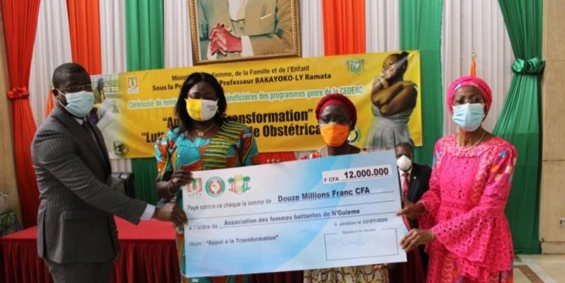 Des bénéficiaires tenant un chèque en compagnie du ministre Ramata Ly-Bakayoko (extrême droite). (DR)