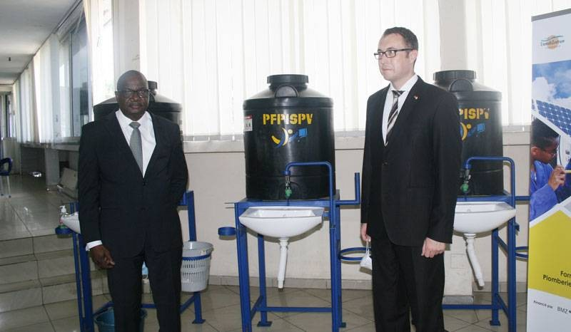 Djedj Mel, directeur de cabinet du Secrétariat d'Etat en charge de la Formation professionnelle et Benjamin Laag, premier secrétaire de l'Ambassade de l'Allemagne à Abidjan, devant les dispositifs de lavage des mains. (DR)