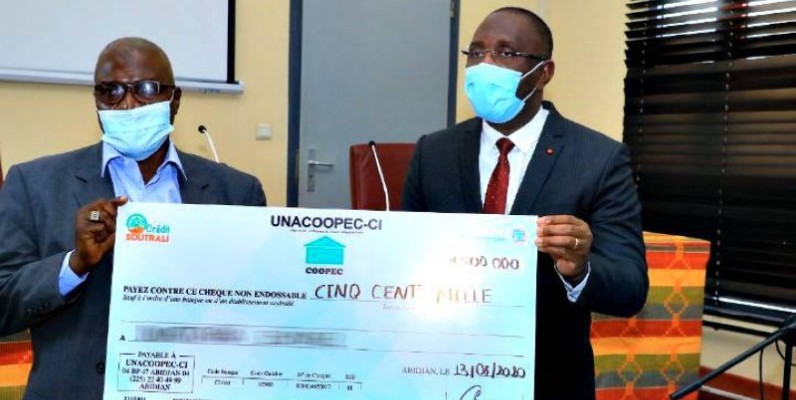 Diarrassouba Souleymane, ministre du Commerce remettant un chèque à un commerçant. (DR)