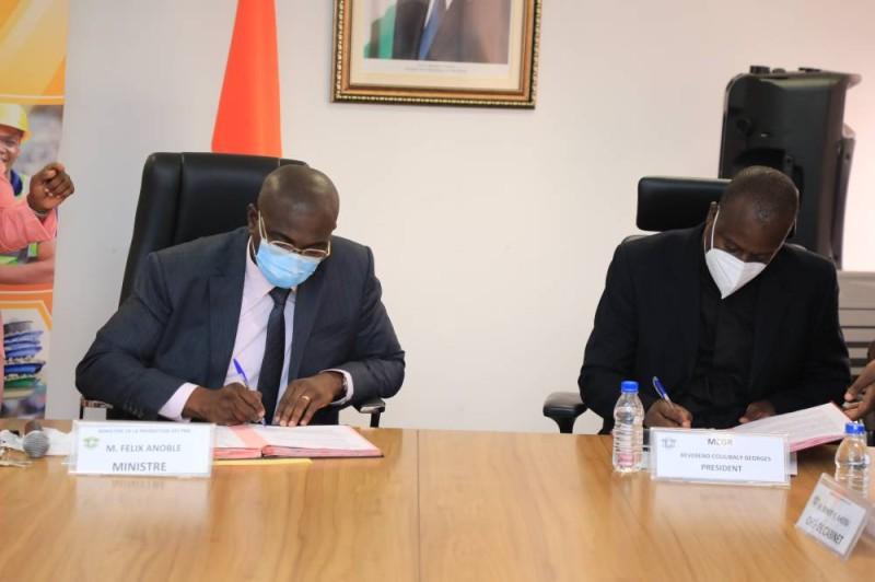 Le ministre de la Promotion des Pme, Félix Anoblé (à gauche) et le président de la Mutuelle du collectif des guides religieux, Georges Coulibaly, parafant le document du partenariat. (DR)