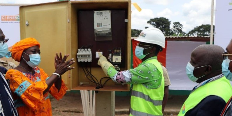 Diomandé Vagondo connectant officiellement le village au reseau électrique national à la grande joie de Mariatou Koné. (Saint Tra-Bi)