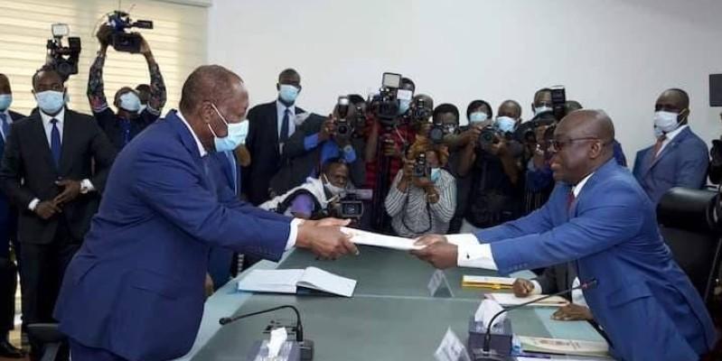 Le Chef de l'Etat, Alassane Ouattara, à gauche, remettant ses dossiers. (Dr)