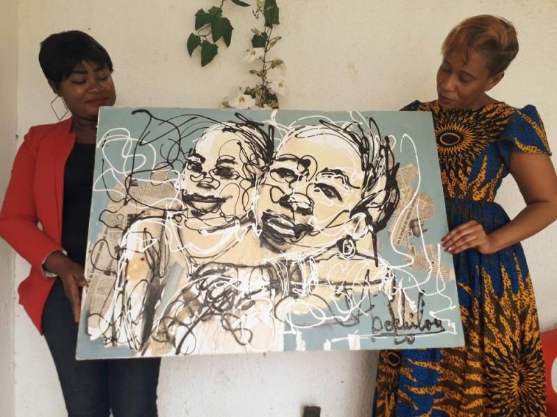 HamiTraoré (à gauche) heureuse de recevoir le tableau des mains de Bénédicte Boéhi Lou. (DR)