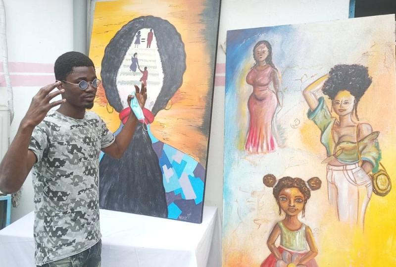 Le jeune peintre Adjé Frédéric Anderson présentant son oeuvre (Ph: Salif D. CHEICKNA)