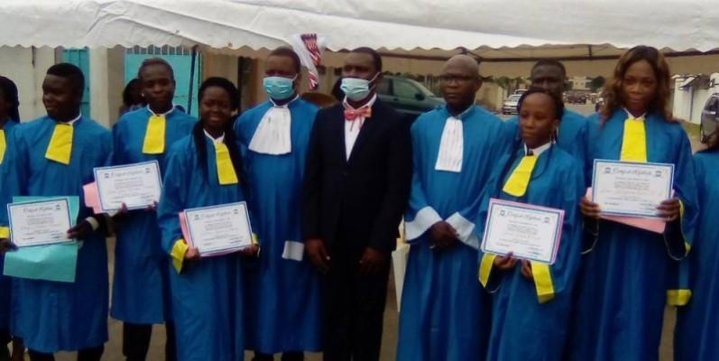 Me Kouassi Okossy Pierre Claver (en noir, représentant la marraine), à sa droite, Me Roméo Babo (directeur de l'Institut), entourés de quelques récipiendaires. (Franc YEO)