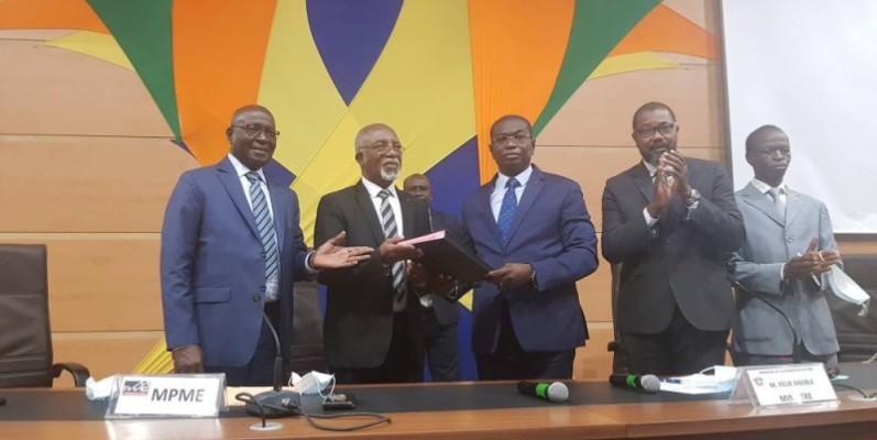 Échange des parapheurs entre le porte-parole des faîtières de Pme, Joseph Amissah (à gauche) et le ministre de la Promotion des Pme, Félix Anoblé. (Dr)