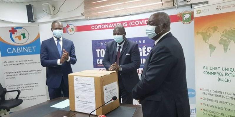 Le Pca du Guce CI, Issouf Fadika (à droite) a remis symboliquement un carton de masques au directeur de cabinet du ministère de la Santé et de l'Hygiène publique, Joseph Acka. (Dr)