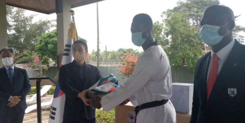 SEM. LEE Sang Ryu remettant un échantillon du lot à Seydou Gbané, capitaine de l'équipe nationale de Taekwondo. (DR)