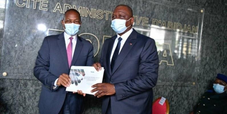 Le Premier ministre Hamed Bakayoko (à droite) recevant le document synthèse des mains du ministre en charge de la construction, Bruno Koné. (DR)