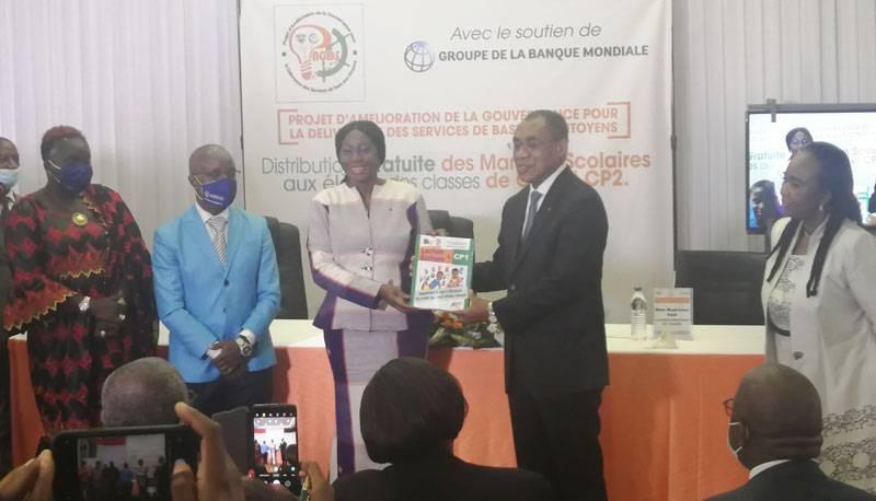 Le ministre de l'Economie et des Finances, Adama Coulibaly, remet symboliquement des manuels scolaires à son collègue de l'Education nationale, de l'Enseignement technique et de la Formation professionnelle, Kandia Camara. (DR)