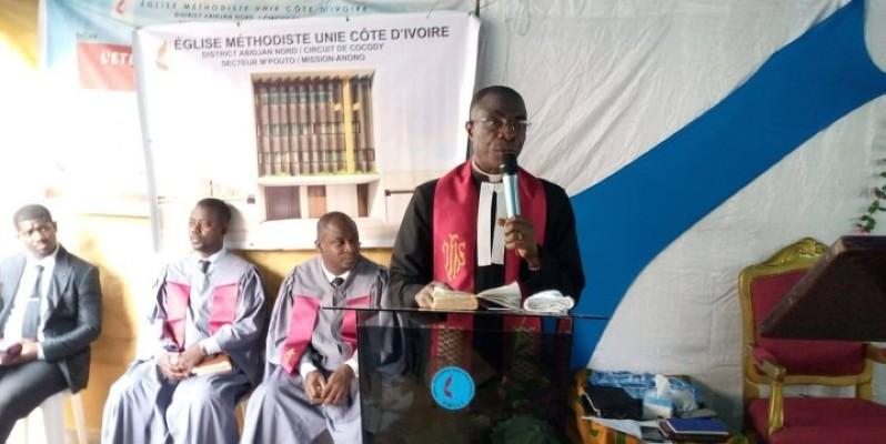 Le Très Révérend Félix Behi, débout, est le pasteur de l'église. (Dr)