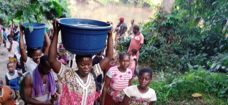 Des Ivoiriennes qui reviennent du fleuve avec de l'eau pour leur bain du soir. (Photos : Saint-Tra Bi)