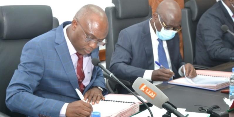 Doffou N'Guessan, directeur général de l'Ins (à gauche) et Ouattara Sié Abou, directeur général de la Dgi, paraphant l'accord de partenariat scellé, hier. (Dr)