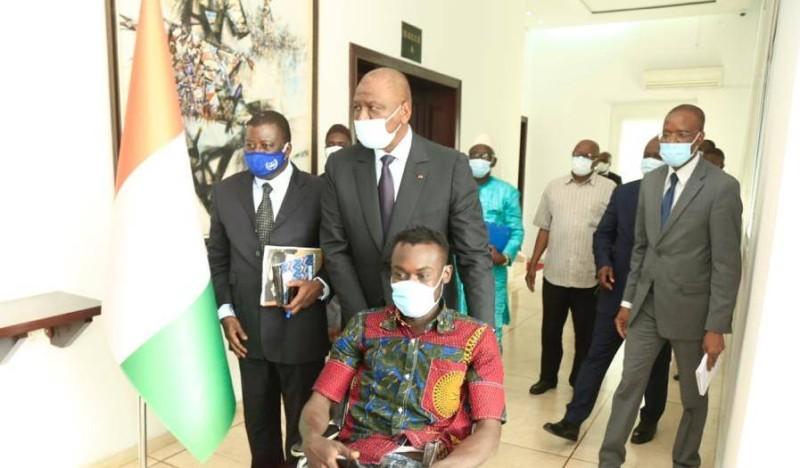 Le 1er ministre Hamed Bakayoko en compagnie d'une victime