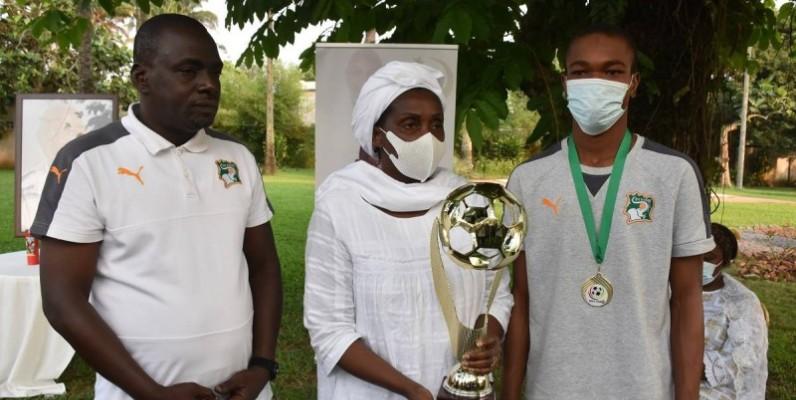 l'épouse de l'ancien président de la Fif a reçu le trophée des mains de l'entraîneur (à gauche) et du capitaine de l'équipe. (DR)
