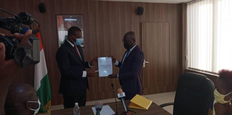 Le ministre Sidi Touré (à gauche) recevant le rapport des mains de Vamara Coulibaly.