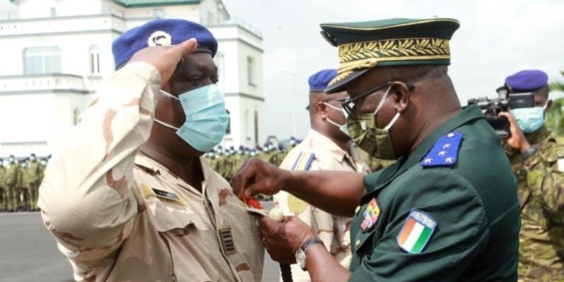 Le chef d'état-major général, le général Doumbia Lassina, procède à la décoration d'un officier des forces armées. (Photo : Sébastien Kouassi )