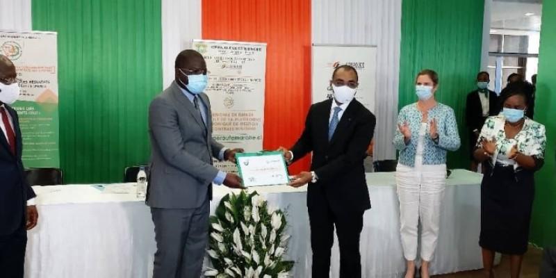 Adama Coulibaly, ministre de l'Économie et des Finances,  remettant symboliquement la plateforme numérique à son collègue Amedé Kouakou. (DR)