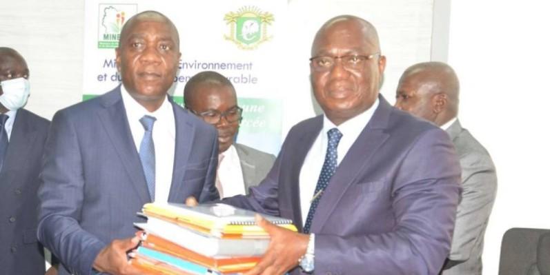 Le nouveau ministre Jean- Luc Assi reçoit les dossiers afférents à son département des mains de François Kouablan, représentant du Pr Joseph Séka Séka, ministre sortant Photo : Dr