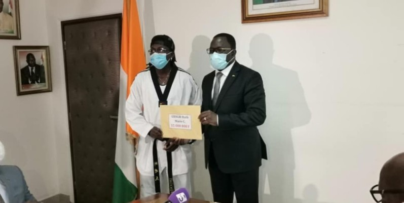 La taekwondo-in Ruth Gbagbi (à gauche) recevant son enveloppe des mains du ministre des Sports et du Développement de l'Economie sportive. (Photo : DR)