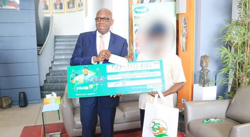 Le Directeur général de la Lonaci remettant le chèque au gagnant. (Photo : DR)
